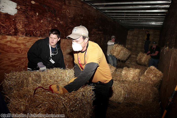 Elder Cottrell, left, and Richard McMahon unload bales of straw to be bagged, palletized and mailed at Airland Transport in Anchorage for the 22 checkpoints along the Iditarod trail Thursday, Feb. 7, 2013.