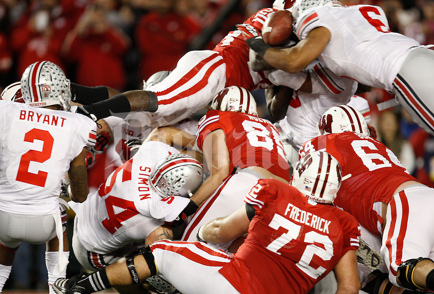 Ohio State Buckeyes linebacker Etienne Sabino (6) and Ohio State Buckeyes linebacker Ryan Shazier (10) tackle a jumping Wisconsin Badgers running back Montee Ball (28) as he tries to jump in the endzone forcing a fumble into the hands of Ohio State Buckeyes defensive back Christian Bryant (2) in the fourth quarter of the NCAA football game at Camp Randall Stadium in Madison, WI, Saturday afternoon, November 17, 2012. The Ohio State Buckeyes defeated the Wisconsin Badgers in overtime  21 - 14. (The Columbus Dispatch / Eamon Queeney)