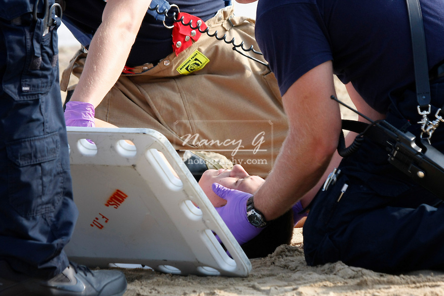 EMTs at a scene of a mass casualty incident helping victim onto a backboard