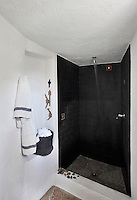 The walls of the simple walk-in shower are lined with slate tiles