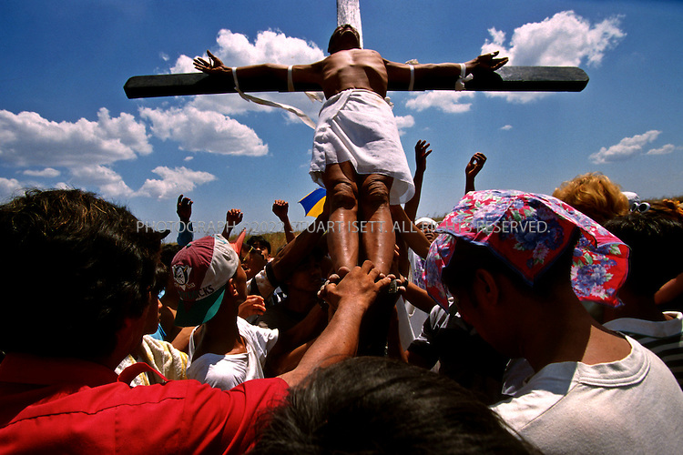 4/21/2000--San Fernando, Philippines..San Fernando is world-famous for its annual Easter re-enactment of the crucifixion of Jesus Christ. The Roman Catholic devotees were crucified in batches, their palms and feet attached to crosses with 10cm nails soaked in alcohol to prevent infection, to repent sins, pray for a sick relative or fulfill a vow, organizers said. the festival also features local men whipping themselves in penance, sending up showers of blood on visitors..Photograph ©2007 Stuart Isett. All rights reserved.