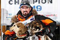 Pete Kaiser poses with his Marrow (L) and Lucy at the Nome finish line after winning the 2019 Iditarod Trail Sled Dog Race. Pete's winning time is 9 days 12 hours 39 minutes and 6 seconds<br /> <br /> Photo by Jeff Schultz/  (C) 2019  ALL RIGHTS RESERVED