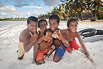 i-Kiribati children posing for the camera in a village on the island of Kiritimati in Kiribati
