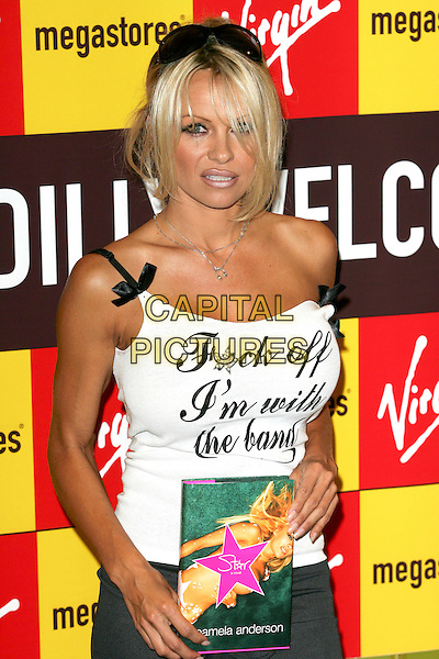 "PAMELA ANDERSON.Signs copies of her new book, a novel, ""Star"" at Picadilly Virgin Megastore, London,.21st October 2004.half length silver necklaces sunglasses on head slogan top vest black and white ribbons bows ""Fuck off I'm with the Band"" .Ref: BR.www.capitalpictures.com.sales@capitalpictures.com.©Capital Pictures."