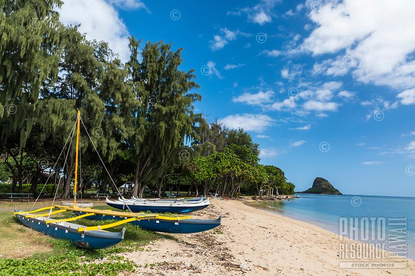 Hawaiian outrigger canoes at Kualoa Regional Park, with Chinaman's Hat in the distance, Kane'ohe Bay, O'ahu.
