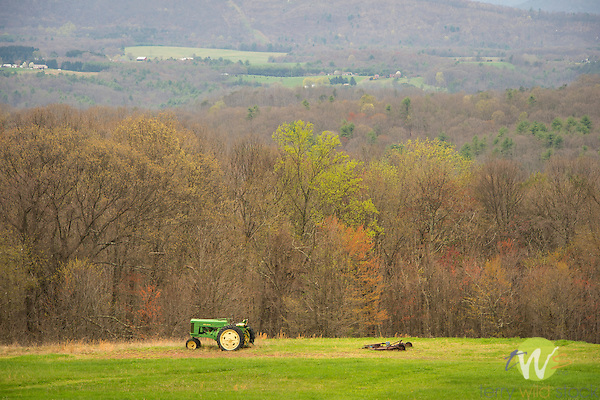 Old John Deere tractor in field and spring landscape.