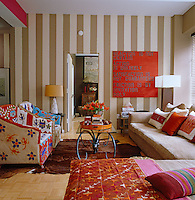 The soft furnishings and artwork add splashes of bright colour to the beige and cream striped wall in the living room