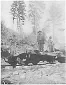 3/4 view of a D&RG flat car equipped for hauling logs with two workers loading logs.