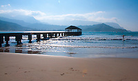 Surfing, swimming and boating near the pier are popular activities at Hanalei Bay Beach Park on the North Shore of Kauai. The island's mountains and the cliffs of Na Pali loom in the background.