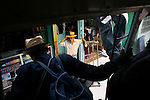 GUATEMALA  --  FEBRUARY 3, 2007:   A man waits to transport a load from a bus as passengers leave through the rear emergency exit at a bus depot on February 3, 2007 in Nebaj, Guatemala.  (PHOTOGRAPH BY MICHAEL NAGLE)