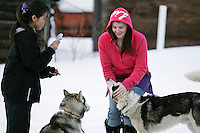 Janann Capsul takes a photo while Misty Wachter pets a dog from Susan Ramsteads team on Thursday evening.  Both are residents of Takotna.