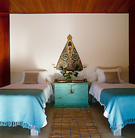 The twin-bedded guest bedroom has a turquoise and white colour scheme