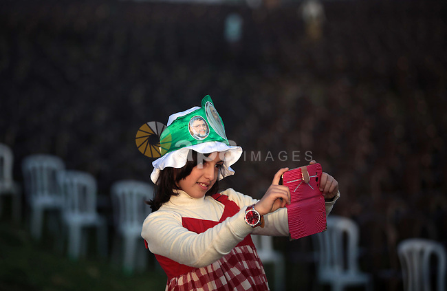 A Palestinian girl takes pictures for the placard depicting late Hamas leaders, during the preparation of the Hamas festival in Gaza City, March 22, 2014. Hamas organized a festival in the anniversary of the death of Hamas leaders Sheikh Ahmed Yassin, Ibrahim Makadmeh, and Abdul Aziz Rantisi. Photo by Ashraf Amra