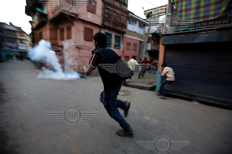 Police and paramilitary chase stone throwing youth through alleyways, following protests over the arrest of  separatist leader Muhammad Yaseen Malik. Srinagar, Kashmir, India. © Fredrik Naumann/Felix Features