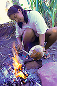 Koatinemo village, Brazil. Assurini Indian woman, Maye, applying vegetable glaze; resin from the Jatoba tree, over a fire.