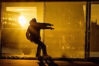 Nederland, Amsterdam, 17 jan 2016<br /> Skater oefent zijn skills voor een raam waar de ondergaande zon in reflecteerd en een gele gloed geeft.<br />  <br /> Foto: (c) Michiel Wijnbergh