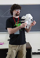 New York, NY, USA - June 26, 2011: Mike Assis, original Origami designer at the OrigamiUSA Convention in New York City holding one of his complex creations, a mouse, folded from one square of paper without cuts.