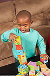 Two year old toddler boy stacking blocks making tower
