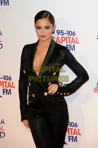 Cheryl Cole.attending the Jingle Bell Ball, o2 Arena, London, England, UK, .8th December 2012..half length black tuxedo jacket  catsuit buttons brass gold low cut  red lipstick make-up  no bra cleavage plunging neckline hand on hip .CAP/MAR.© Martin Harris/Capital Pictures.