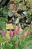 Insekten-Hotel, Insektenhotel in einem Naturgarten, hohle Schilfstängel, Baumscheiben mit Bohrlöchern, Steine mit Bohrlöchern sowie ein Lehmangebot bieten Nistmöglichkeiten, Nisthilfen, Nisthilfe für Wildbienen, Mauerbienen und solitäre Wespen