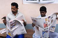 INDIA Karnataka Moodbidri, men read newspaper in Kannada language / INDIEN Maenner lesen lokale Zeitung in Kannada Sprache