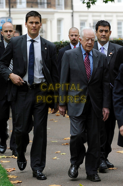 Jimmy Carter (James Earl Carter Jr.)  Spotted walking in central London, England. .5th October 2011.full length black suit blue shirt red tie former president of the United States politics walking minders security guards .CAP/IA.©Ian Allis/Capital Pictures.