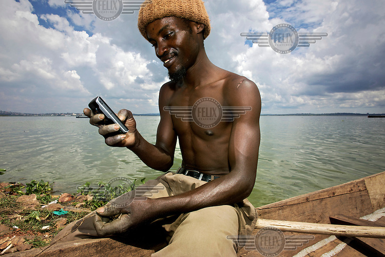 A young fisherman uses his mobile phone at Ggaba landing site on the shore of Lake Victoria in Kampala.