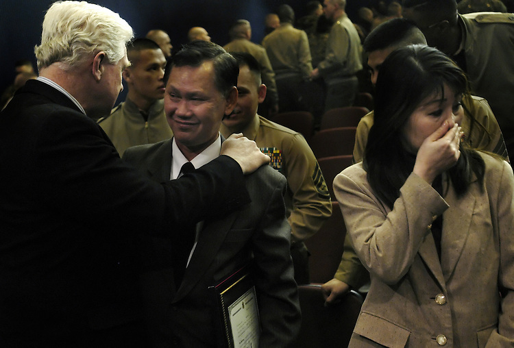 The parents of Corporal Binh Le, Lien Van Tran, and Kim Hoan Thi Nguyen, are comforted by Rep. Jim Moran, D-Va., after a ceremony for Le's posthumous U.S. citizenship at the Navy Annex in Arlington, Va. Le, a Vietnamese Marine, was killed in Iraq on his second tour of duty while preventing a suicude bombing attack,