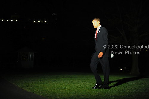 Washington, DC - December 1, 2009 -- United States President Barack Obama walks across the South Lawn after arriving at the White House in Washington on Tuesday, December 1, 2009. President Obama traveled to West Point Military Academy in New York and spoke on a planned increase of troops and exit strategy for the war in Afghanistan. The buildup is targeted to reverse the Taliban advances in the country and to train Afghan soldiers and police. .Credit: Alexis C. Glenn / Pool via CNP