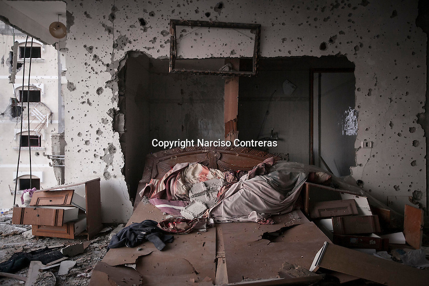 "n this Sunday, Aug. 17, 2014 photo, a bedroom destroyed by heavy artillery is seen in Shuyaja neighborhood after it was hit during the ""Protective Edge"" Israeli military operation in Gaza Strip. (Photo/Narciso Contreras)"