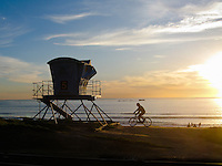 Riding a Bike Along the Beach at Sunset