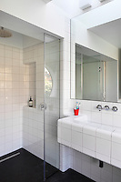 A minimalist white tiled bathroom with a mirror above a functional washbasin and a shower are with a glass screen.