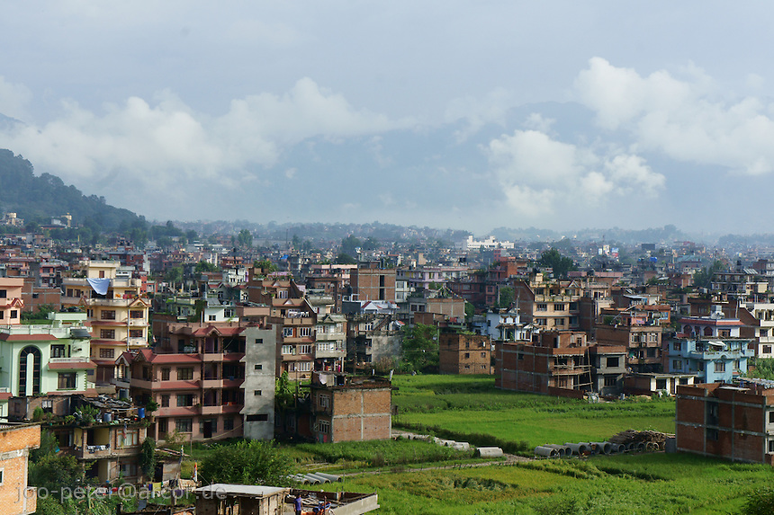 city view of Kathmandu at the border of the city with less dense developement, showing typical architecture, brick-stone buildings with several stores, rice fields in between. Alle the Kathmandu valley is developed similar.