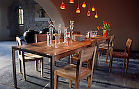 A collection of glass candlesticks on a contemporary wooden dining table in the dining area