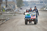 Men push a cart through Mosul, Iraq, on January 27, 2017. The Islamic State group occupied the city in 2014. It was liberated in early 2017.