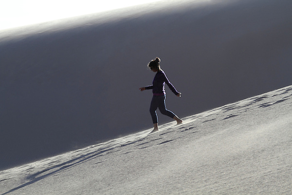 Woman walking downhill at Great Sand Dunes National Park, Alamosa, Colorado, John offers private photo trips to Great Sand Dunes National Park and all of Colorado. All year long.