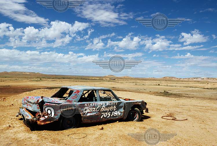 A wrecked and abandoned car painted with the sign 'Opal Buyer' in the desert near Coober Pedy.  The area is the capital for opal mining in Australia.