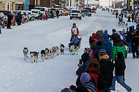 Lisbet Norris leads Marcelle Fressineau into the finish chute to claim 48th place at Nome on Saturday March 15 during the 2014 Iditarod Sled Dog Race.<br /> <br /> PHOTO (c) BY JEFF SCHULTZ/IditarodPhotos.com -- REPRODUCTION PROHIBITED WITHOUT PERMISSION