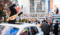 Japan Smile party candidate Maku Akasaka arrives in Shibuya sticking out of the roof of a white Rolls Royce to disrupt another candidates campaigning.