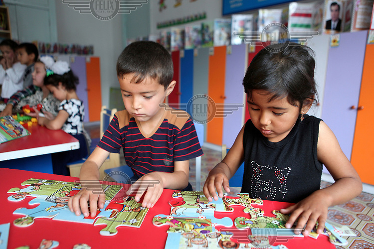 Children playing with a jigsaw puzzle at an Early Childhood Education Centre for four to six year olds in Ispisor Jamoat Village.