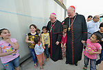 Bishop William Murphy of Rockville Centre (left) and Cardinal Timothy Dolan, the archbishop of New York, are accompanied by children as they walk through a camp for internally displaced families in Ankawa, near Erbil, Iraq, on April 9, 2016. Murphy and Dolan, both board members of the Catholic Near East Welfare Association, are in Iraqi Kurdistan to visit with Christians and others displaced by ISIS.