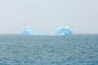 Fog shrouded iceberg floating in Prince William Sound. Summer in Southcentral Alaska.