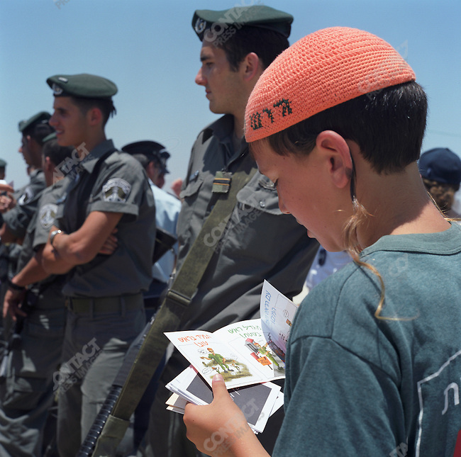 Israel Disengagement: a young boy wearing a fluorescent orange yarmulke (or kippa) in the offical color of the 'No to Disengagement' movement, looks at a homemade brochure created by kids to be given to IDF soldiers explaining their reasons why the withdrawal in unjust and why the soldiers must not participate. Gaza Strip, July 2005