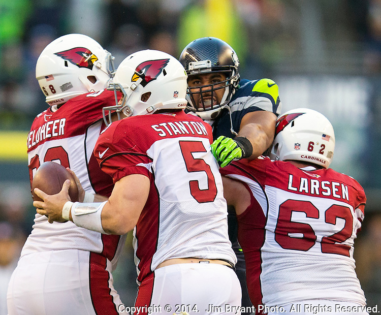 Arizona Cardinals quarter back Drew Stanton (5) scrambles away from the pass rush of Seattle Seahawks defensive tackle Jordan Hill (97) at CenturyLink Field in Seattle, Washington on November 23, 2014. Blocking Hill is tackle Jared Veldheer (68) and center Steve Larsen (62).  Stanton completed 14 of 26 passes for 149 yards and had one interception in the Cardinals 3-19 loss to the Seahawks. ©2014. Jim Bryant Photo. All Rights Reserved.