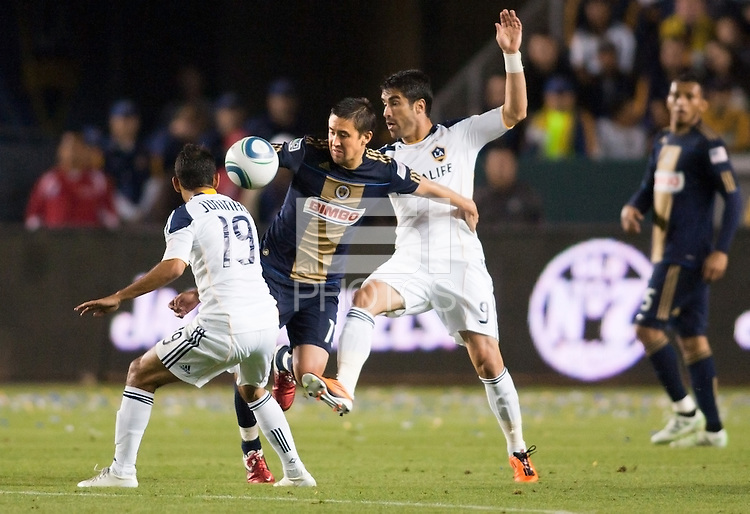 Philadelphia Union midfielder Kyle Nakazawa (13) attempts to move past LA Galaxy players Juninho (L-19) and Juan Pablo Angel (R-9). The LA Galaxy defeated the Philadelphia Union 1-0 at Home Depot Center stadium in Carson, California on  April  2, 2011....