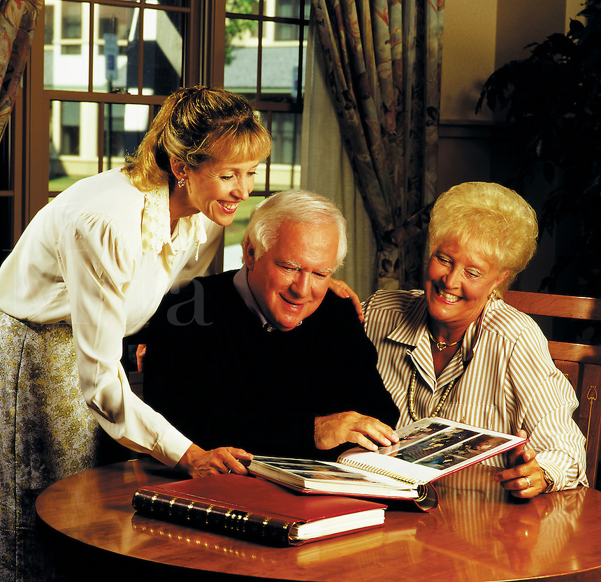 Older couple with adult daughter look over old family photo albums.
