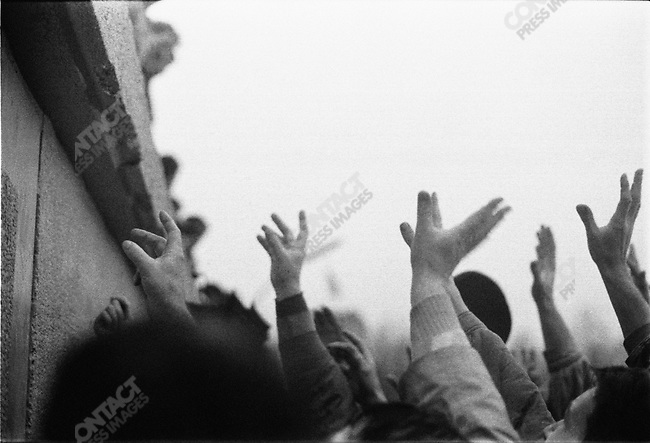 Celebrations at the time of the official opening of the Brandenburg Gate, hands reach for souvenir pieces of the Berlin Wall Berlin, Germany, December 1989