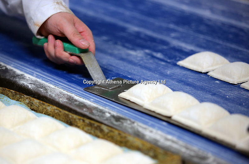 Pictured: Patries are lifted in a spatula after coming out of a cutting machine. Friday 26 May 2017<br /> Re: Lewis Pie and Pasty Company which has gone into halal products in Swansea, Wales, UK