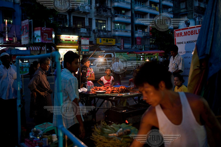 People buy fried chicken from a food stall in Yangon.