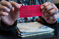 "Isabel Lopez, 50, of Hyde Park, Boston, Massachusetts, holds a card given out to area immigrants as part of ""Know Your Rights"" efforts by advocates of immigrants. Lopez is an independent community organizer who has worked with various organizations in the Brockton, Massachusetts, area for the past 8 years. The card has information about people's constitutional rights and what to say if immigration enforcement officers come to one's home. On one side is English, and on the other side is Haitian-Creole."